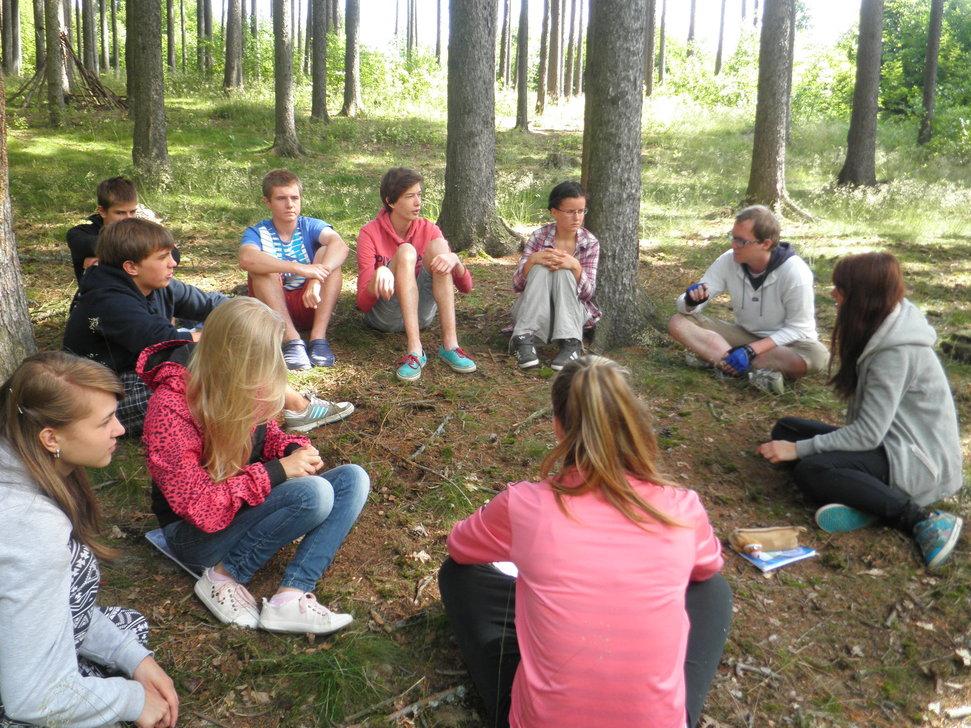Děti sedící v přírodě na dopolední výuce angličtiny